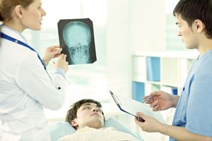 Young man lying in hospital with head injury, doctor examining his brain x-ray