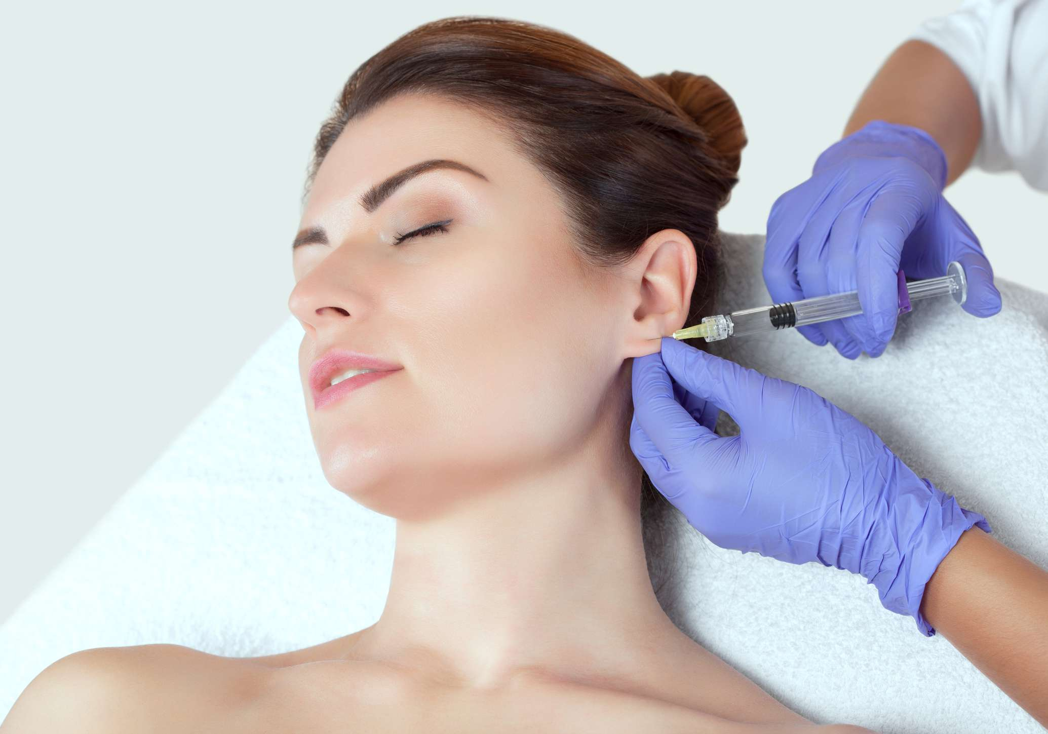 Woman receiving an injection in her ear lobe