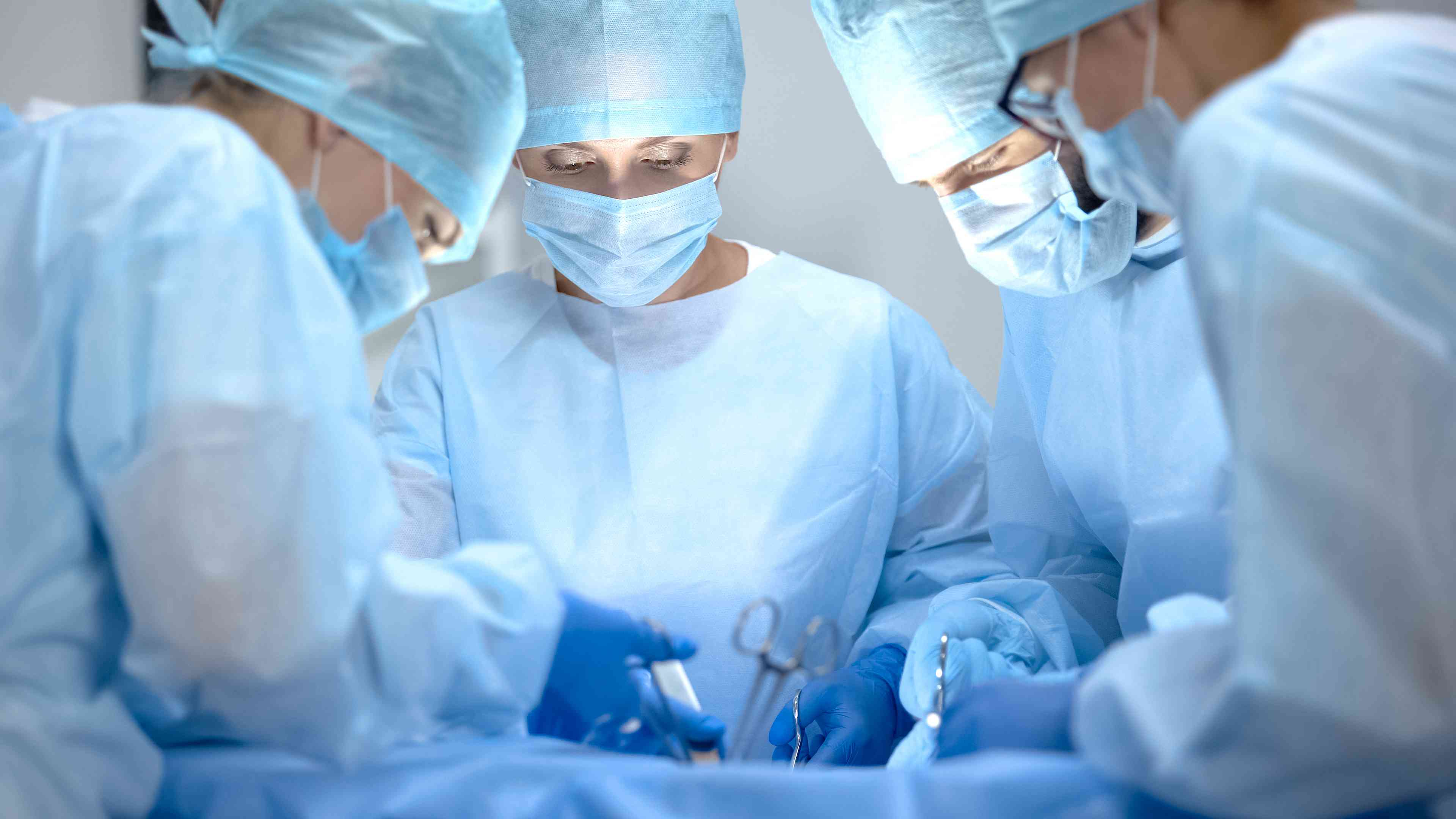 Surgical operating team performing surgery in modern hospital