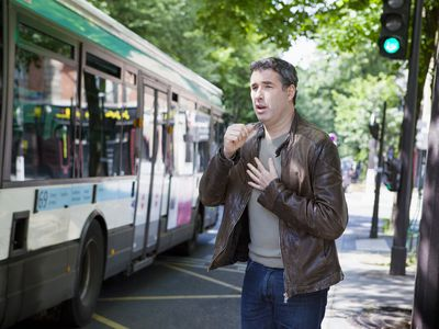 Man with asthma coughing at bus stop