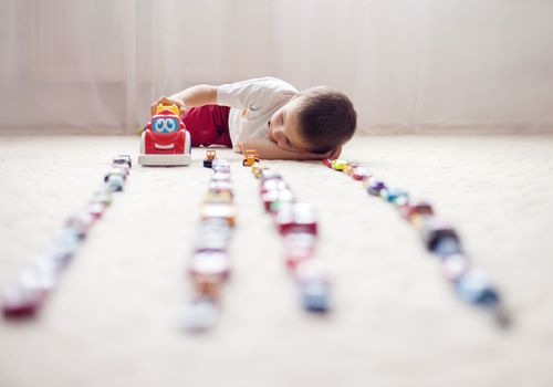 Cute little boy, playing with toy cars at home