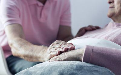Man holding elderly woman's hand