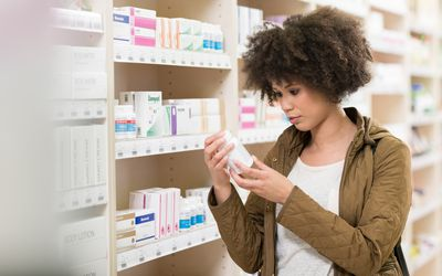 A woman looks at supplements in a drug store.