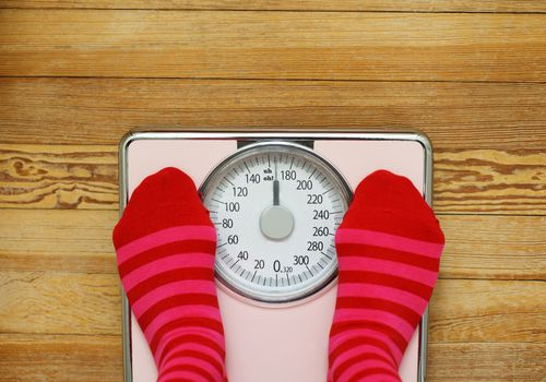 Pink striped socks standing on pink weight scale.