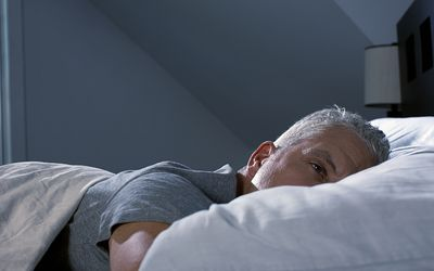 Man lying awake in bed due to symptoms of insomnia