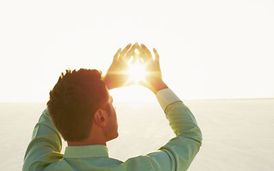 Man framing sun with hands.