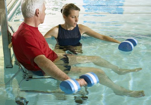 man working in pool therapy with a young female coach.