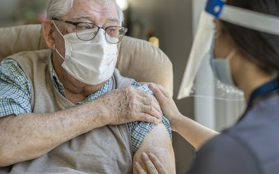 An older adult white man wearing a face mask and glasses. He is holding his sleeve up with a bandaid on his arm where a healthcare worker with a face guard has just given him a vaccine.