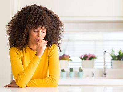 Woman coughing in her kitchen