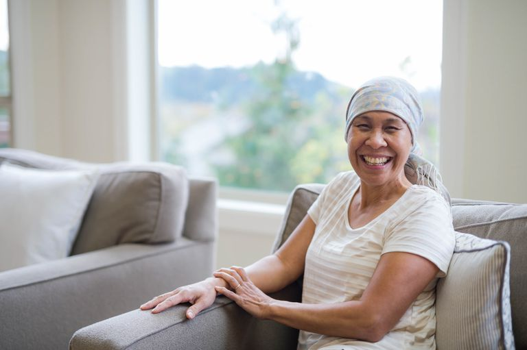 Ethnic adult female with cancer smiling at camera
