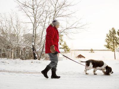 Senior woman walking dog in cold
