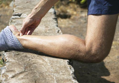 Man pinching his Achilles tendon.