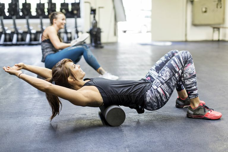 A woman foam rolling her back out
