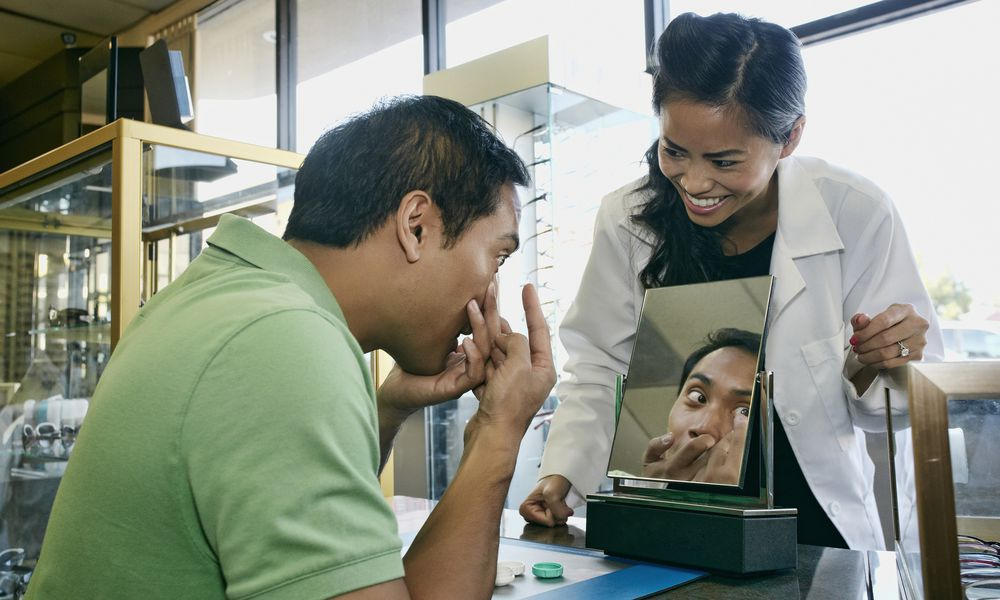 Optometrist helping patient with contacts in office