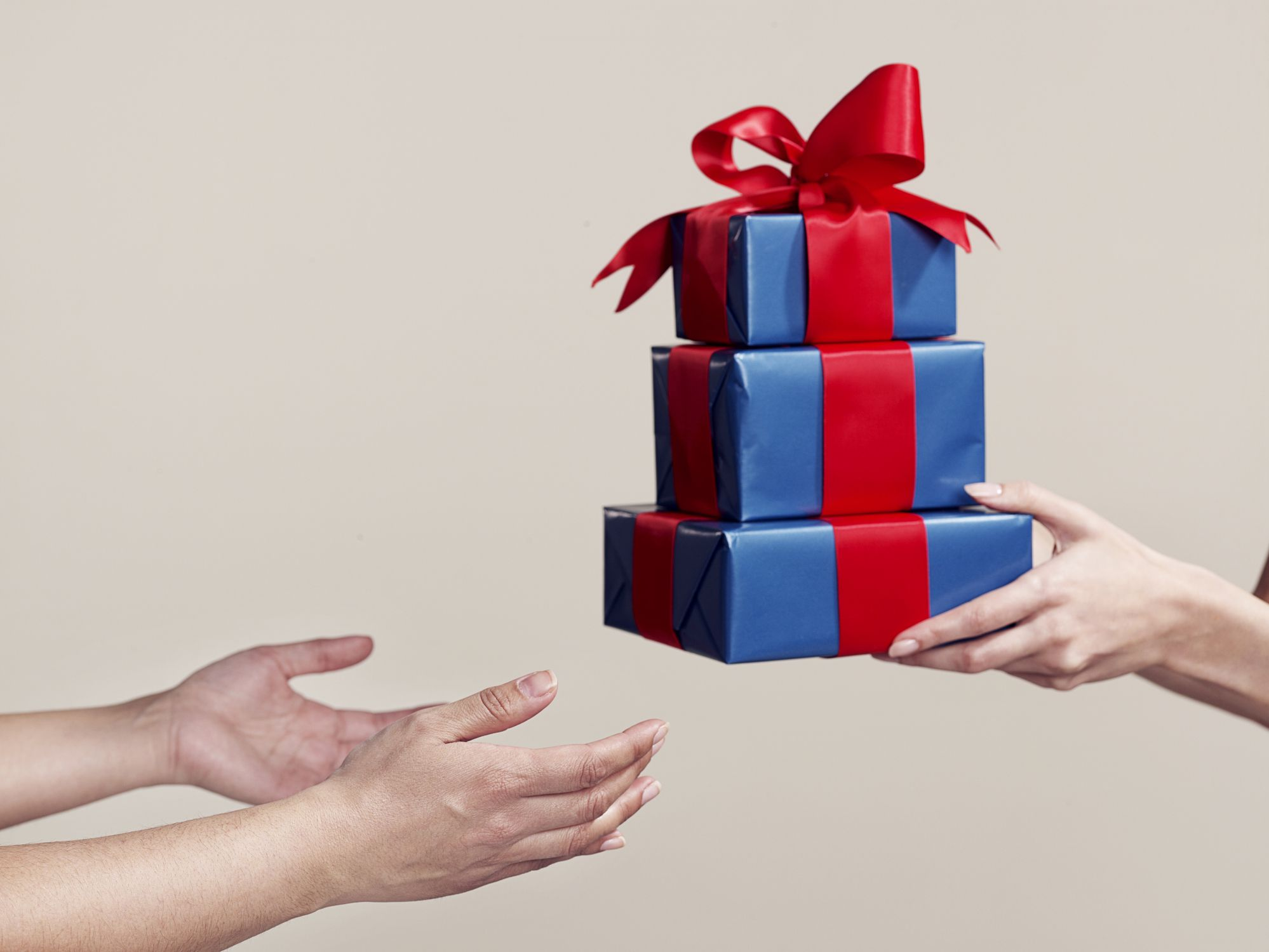 One person handing over a stack of gifts to another