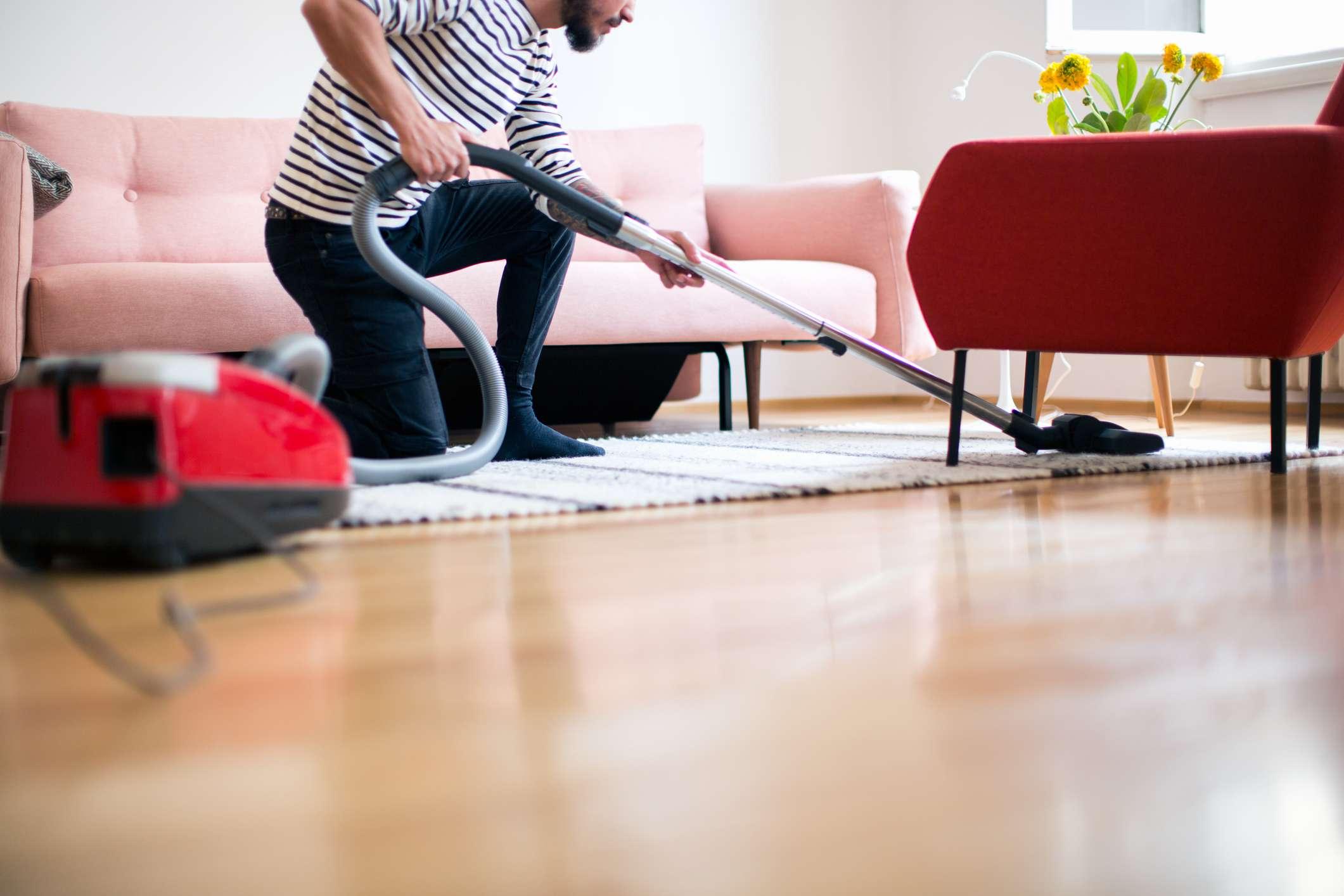 Man kneeling and vacuuming living room