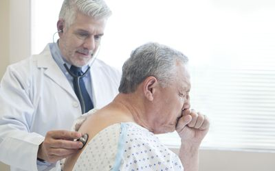 man coughing while doctor checks