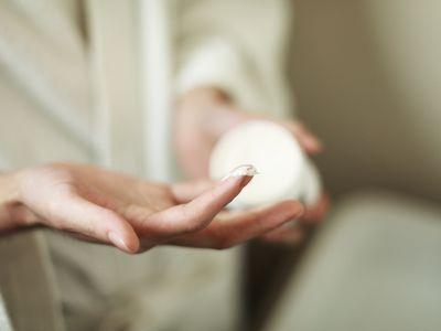 Hands holding jar of cream