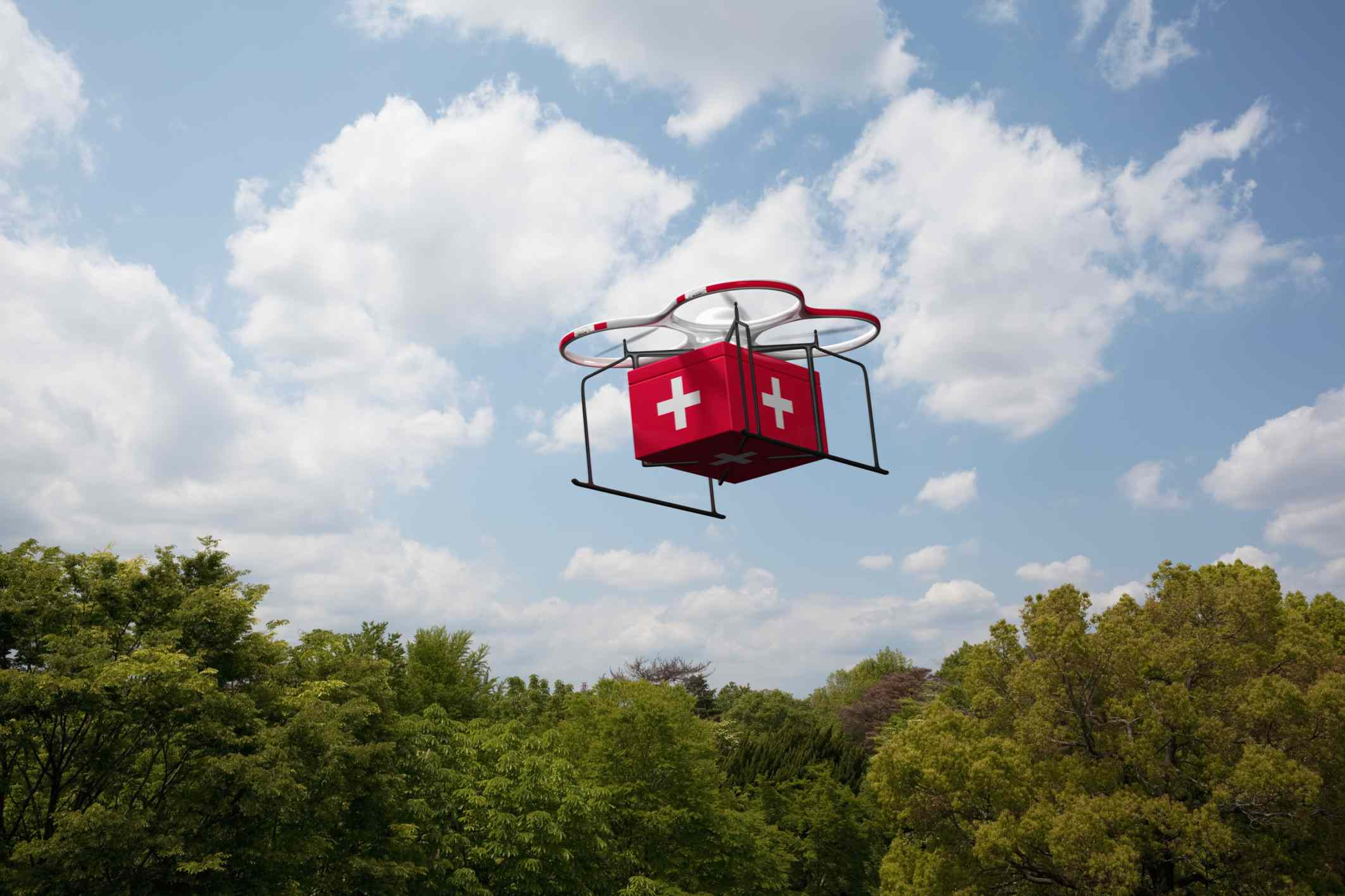 Drone carrying a first aid box above a tree line