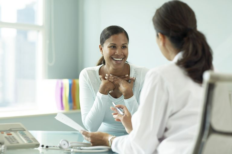 Young woman talking to doctor, smiling