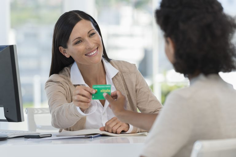 Female doctor giving a health insurance card to a patient
