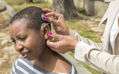 Assisting with a cochlear implant on a woman