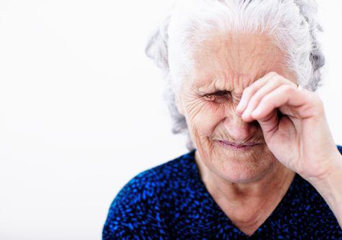 elderly woman rubbing her eye