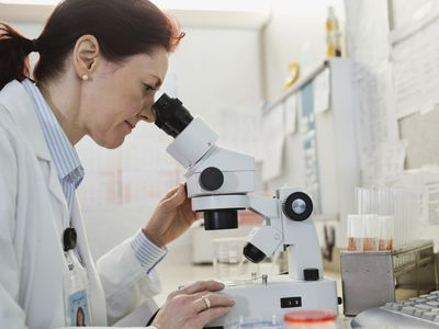 A doctor looks into a microscope.