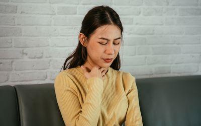 Woman touching throat