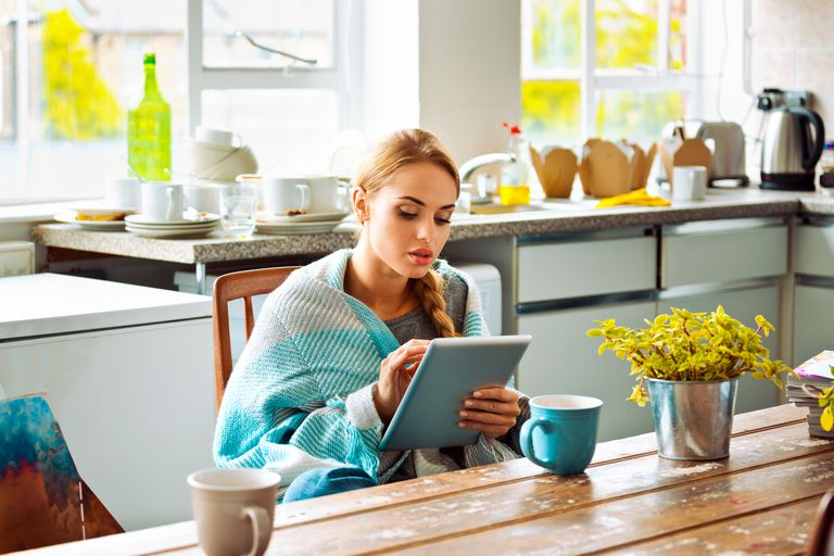 Young woman has a cold, sitting in a kitchen wrapped in blanket and using a digital tablet.
