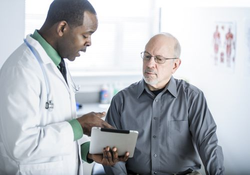 Doctor showing patient results on a tablet.