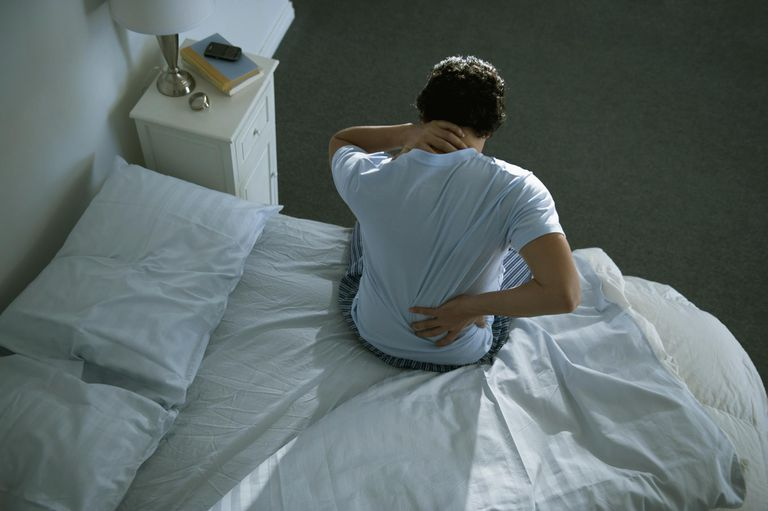 Man with back pain getting out of bed