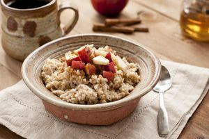 A bowl of oatmeal with apples, honey, and cinnamon