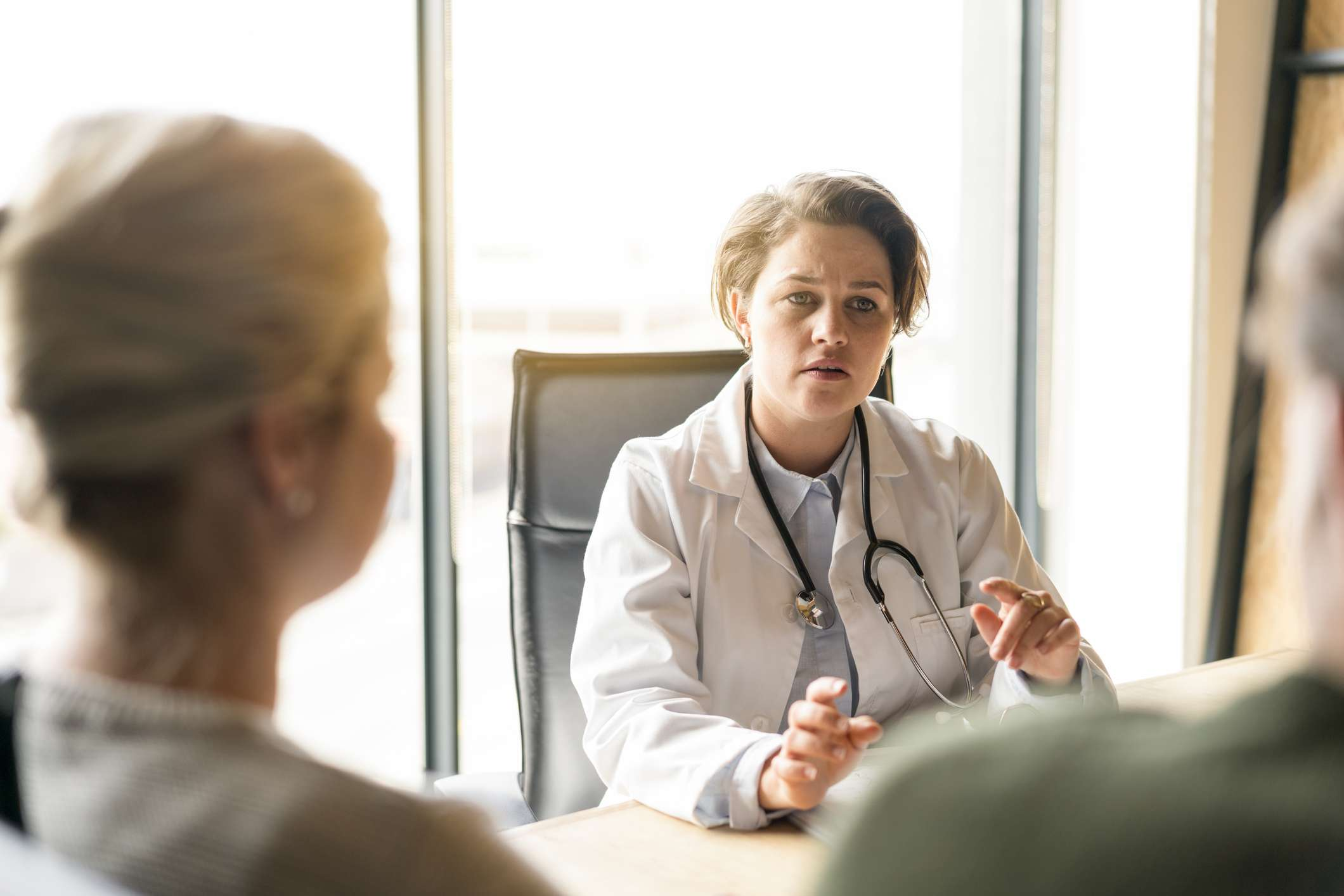 Female doctor talking with mid adult couple in clinic