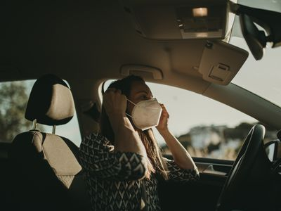 Woman wearing face mask in the car.
