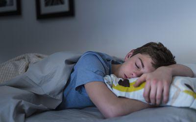 Teen boy asleep in bed