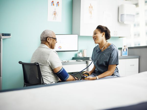 Happy female doctor checking male patients blood pressure in clinic