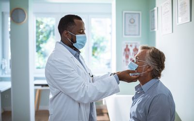 Doctor treating a patient, both are wearing masks.