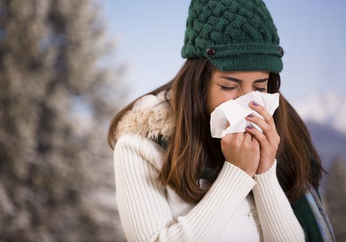 woman with flu or allergies sneezes while outside