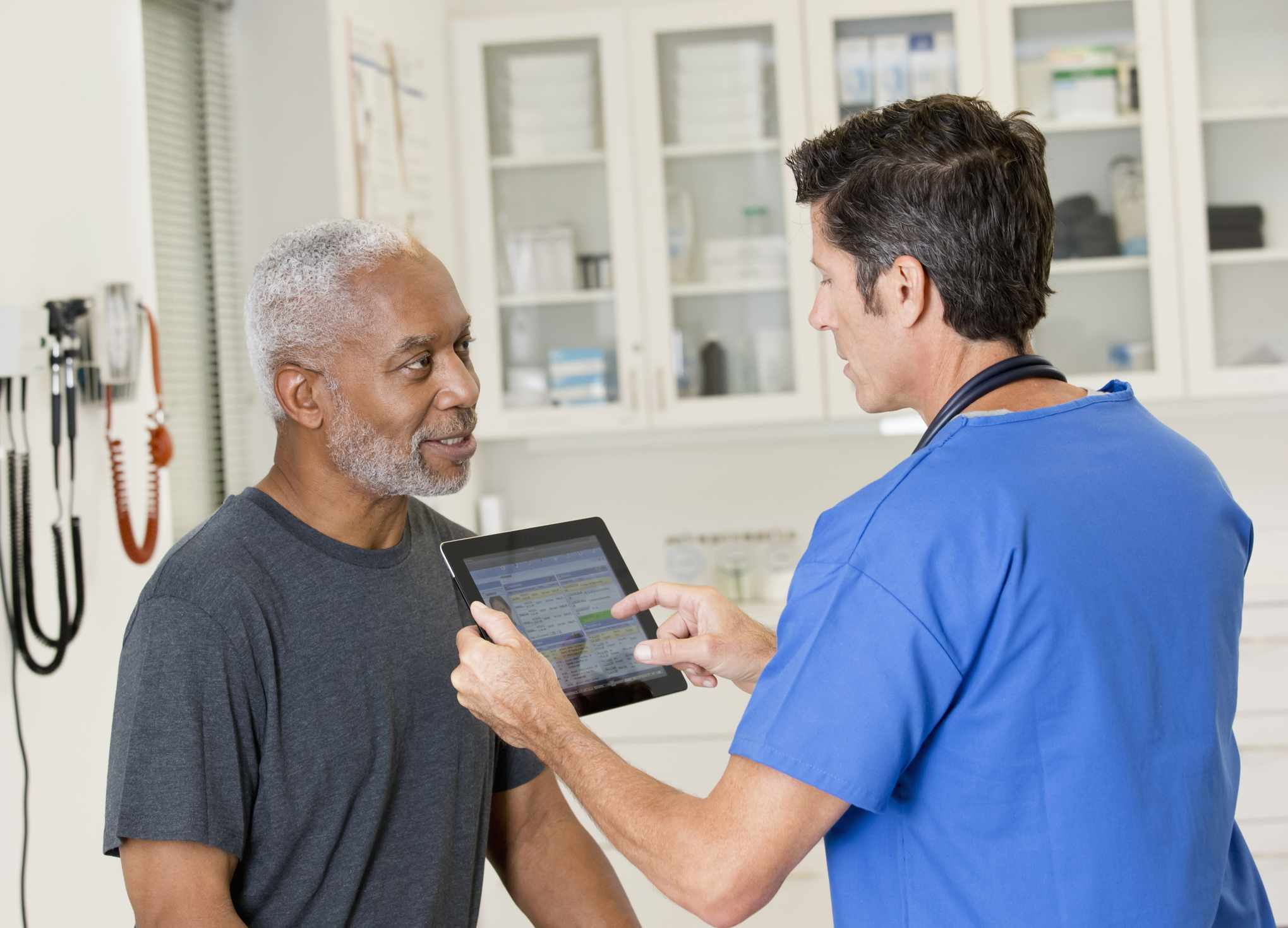 Doctor on iPad talking with patient in his office