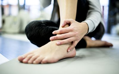 Young woman having ankle pain