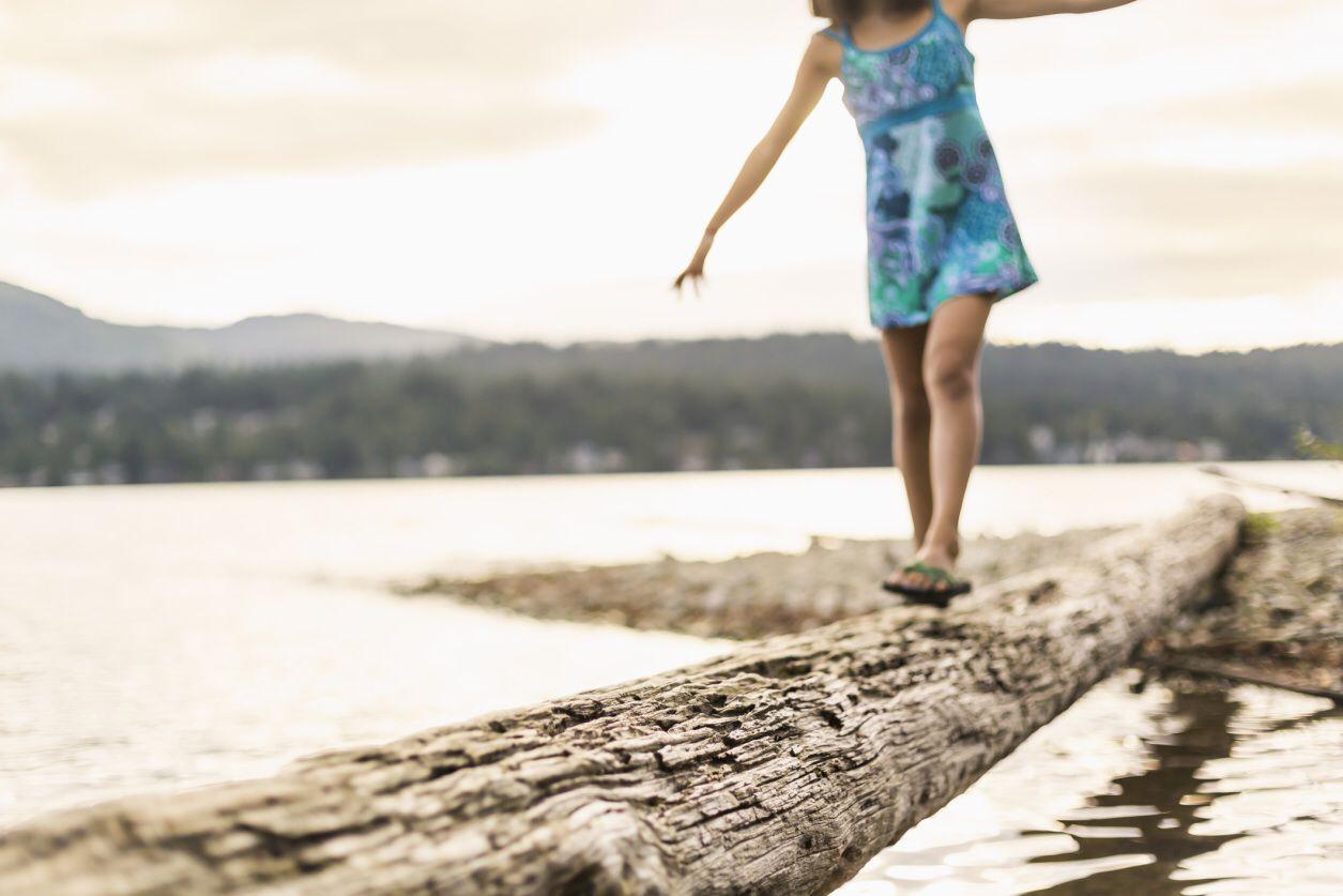 Girl balancing on a log.