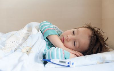 a sick child lying in bed