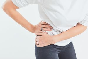 woman holding her hip in pain