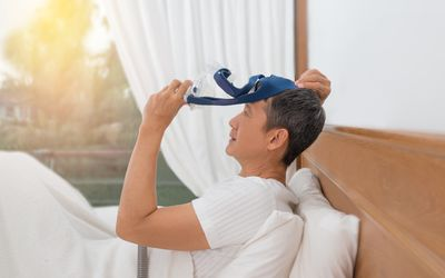 Side View Of Patient Wearing CPAP Mask for Sleep Apnea While Sitting On Bed
