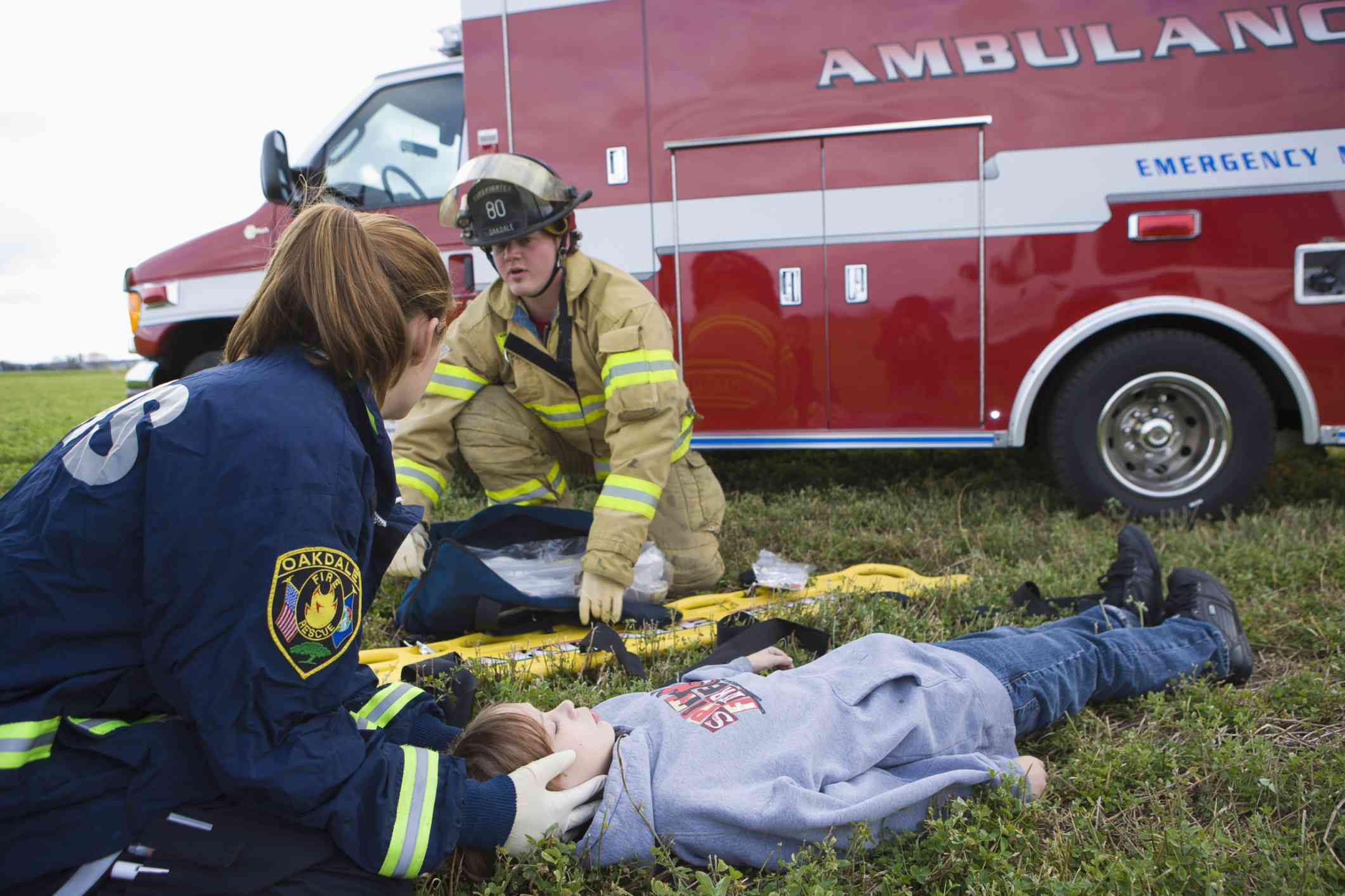 A group of Emergency Medical Technicians working on a patient in a field rescue