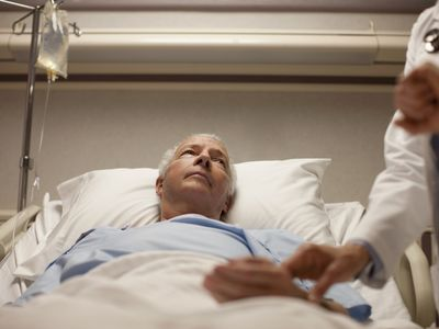 doctor taking pulse of senior man in hospital bed