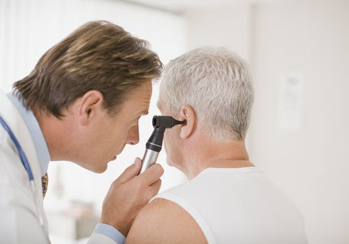 Doctor examining male patient's ear in doctors office