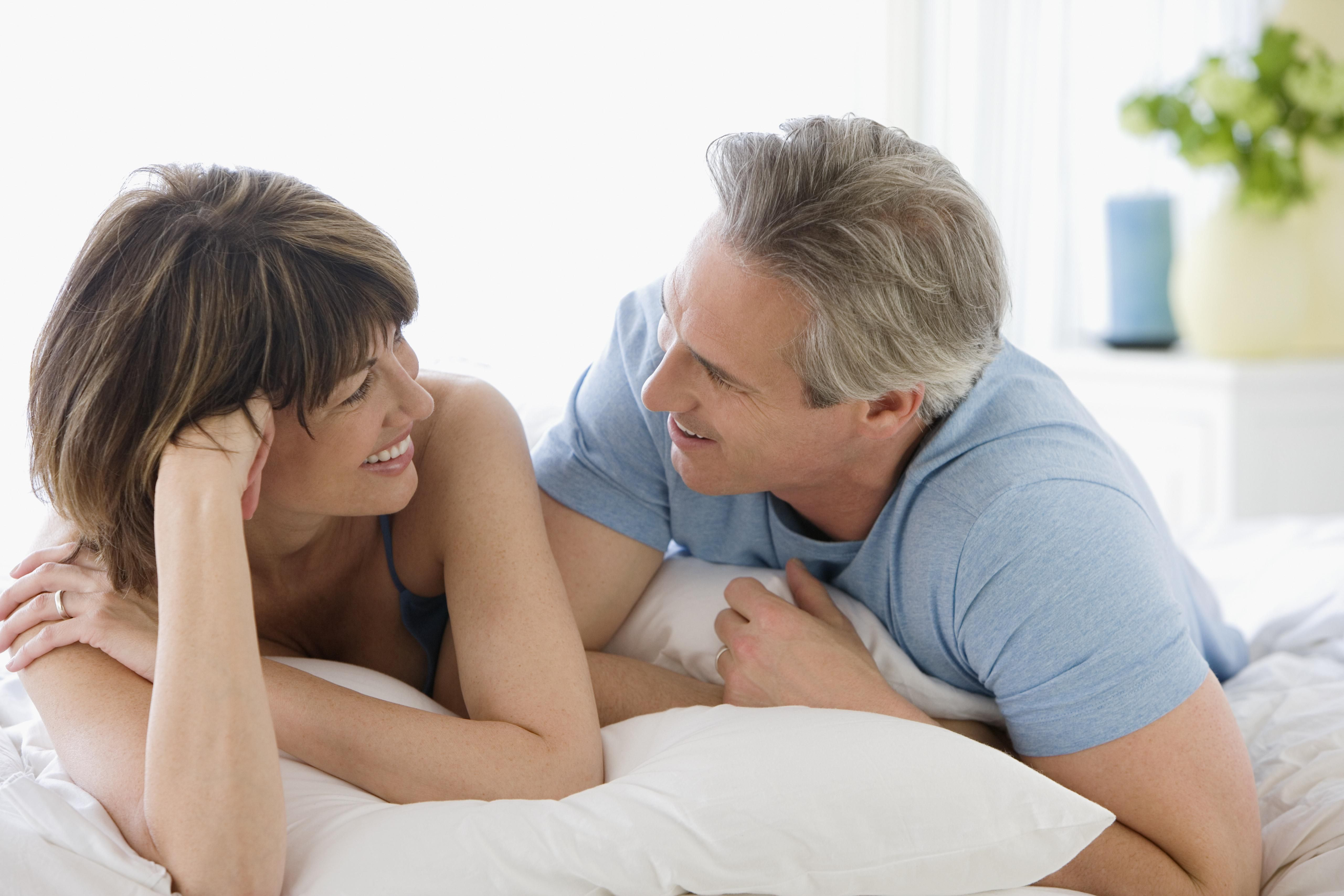 Mature couple smiling at each other in bed