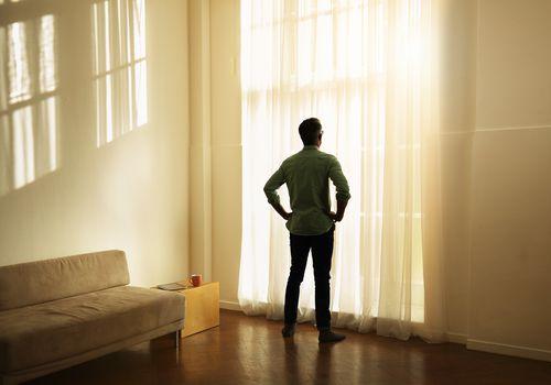 Man Alone Watching Dawn from a window inside